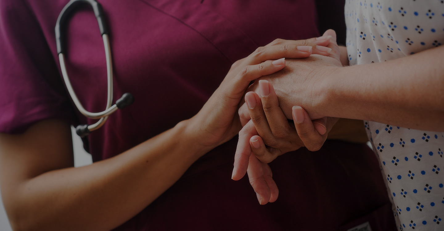 A nurse holding the hands of a diabetic patient to provide comfort and support