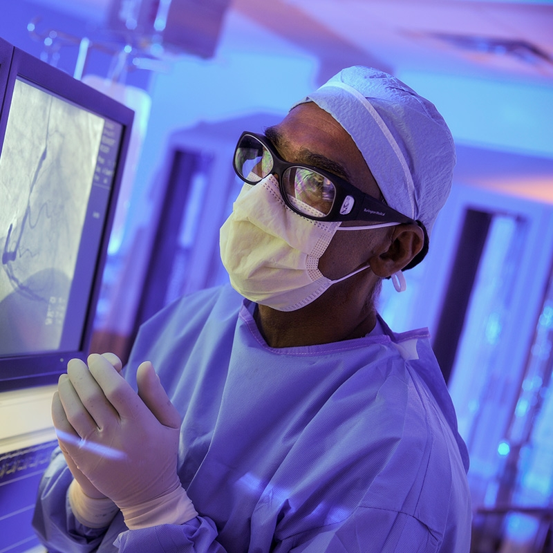 Endocrinologist in operating attire reviews imaging results for a diabetic patient