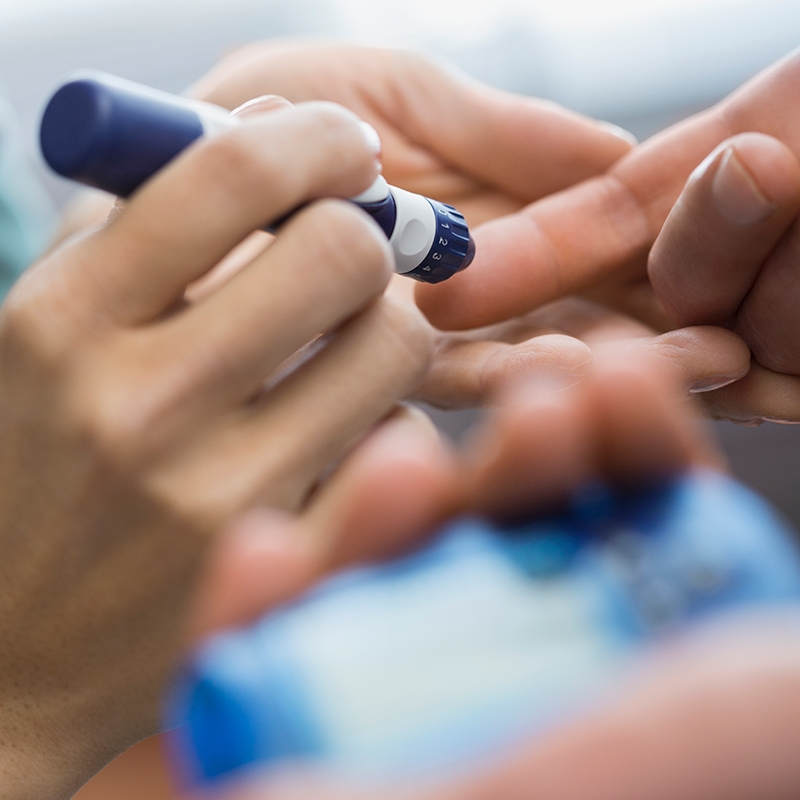 A healthcare practitioner administers an injection to a patient's finger with an insulin pen