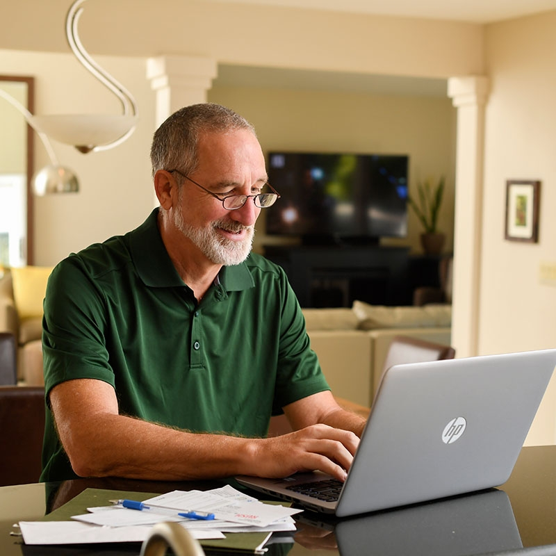 A man reviews additional diabetic health resources on his computer in a home office